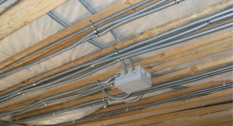 В каркасном доме электропроводка делается в металлическом кожухе.